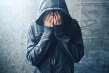Hooded Person Hiding Face in Hands