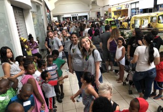 Krazy Coupon Lady employees and children stand in line for Build-A-Bear event