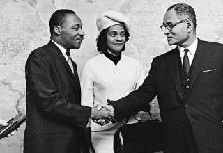 Dr. King and Mrs. King shake hands with Ralph Bunche at the United Nations