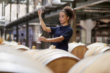 Young woman testing wine in a wine factory warehouse