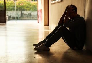 Depressed Person in Shadowy Hallway