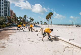 Scientology Volunteer Ministers, shoveling the sand off beachside sidewalks after Hurricane Irma struck Clearwater Beach.