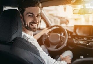Friendly Driver Smiling from Front Seat of Car
