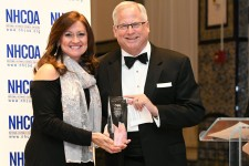 Cindy Padilla, board chair of the National Hispanic Council on Aging (NHCOA), presents the Ophelia Rinaldi Lifetime Achievement Award to John Feather, Ph.D., CEO of Grantmakers In Aging (GIA)