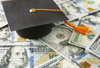 Graduation Cap Sitting on Hundred Dollar Bills