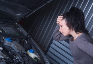 Worried Woman Looking at her Car Engine