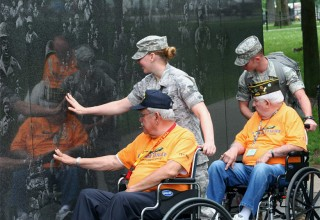 Service members escort WWII veterans at the National Mall in Washington