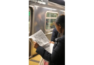Article being read on NYC subway platform