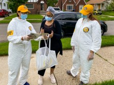 Dressed in their distinctive yellow caps and additional protective gear, Scientology Volunteer Ministers provide Stay Well booklets to help the people of Detroit put the pandemic behind them.