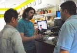 Volunteers enlist help of merchant to place sets of The Truth About Drugs booklets in his shop