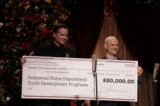 LAPD Hollywood Division Area Commander Captain Cory Palka stepped accepts a $20,000 check from Celebrity Centre Vice President Greg LaClaire—funds raised by the 24th annual Christmas Stories to support Hollywood Police Department programs for at-risk youth.