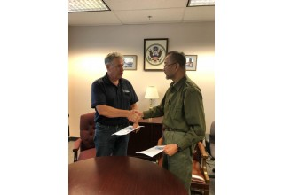 Capt. Edward Nanartowich shaking hands with Mr. Fernando M. Sopot and at the same time sharing each other's signed contract.