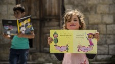 Refugee girl receives a book from Bookwitty