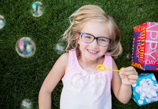 Essilor Vision Foundation young girl with glasses and bubbles