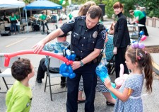 A policeman entertained two children with balloon art at the National Night Out block party at the Church of Scientology Seattle.