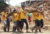 Scientology Volunteer Ministers carry away a massive root under what will now be the foundation of a new home.