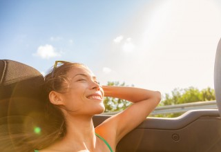 Woman relaxing in car not worried about student loans