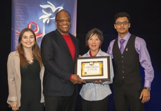 Dr. Sheridan Cyrus receives an award for his contributions to human rights education presented by Nicole Crellin, Youth for Human Rights Toronto Director accompanied by YHR volunteers Kristina Kisin and Abeir Liton.