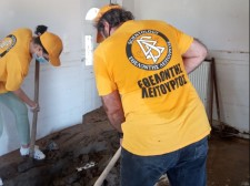 Volunteer Ministers do the arduous work of digging up dried mud that has hardened into a dense mass in a local home.