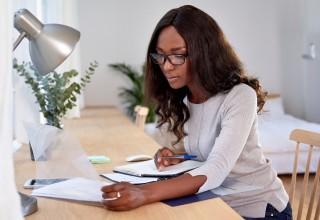 Woman Looking Over Her Financials, Working Toward Financial Independence