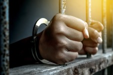 Prisoner with Hands Gripping Bars