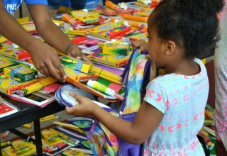 Child Receiving School Supplies
