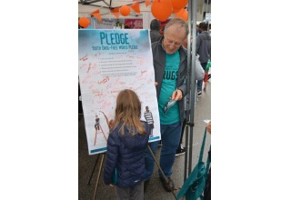 Youngster signs the drug-free pledge at the Drug-Free World booth at British Columbia Recovery Day Festival