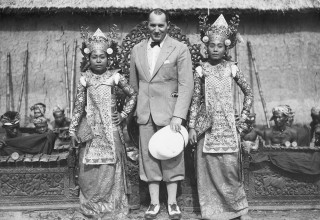 Robert Ripley standing with two Balinese dancers.