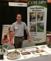 Chris Boyle, owner of 101 Mobility of Denver, stands at his exhibition booth at The Amazing Aging Expo in Denver, Colorado.