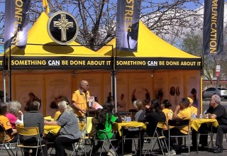 """After lunch, the Scientology Volunteer Ministers delivered their """"Answers to Drugs"""" seminar at their bright yellow tent."""